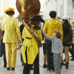 A child asks to touch the tassel of a Tuba player