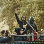 Festival goers dance on a double decker party buss outside the Omni