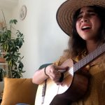 Photo of Silvana Estrada playing guitar and singing